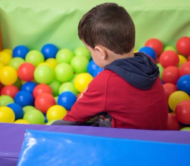 ילד משחק בבריכת כדורים