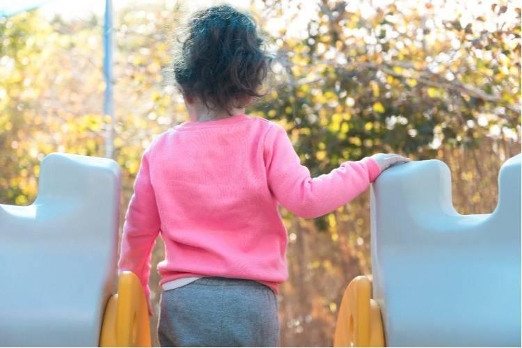 ילדה משחקת בגן משחקים