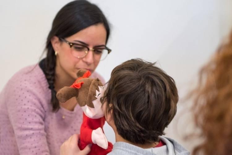 תלמיד מורה משחקים בבובה