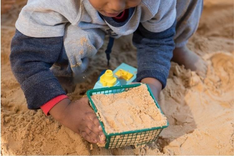 ילד משחק במגרש חול