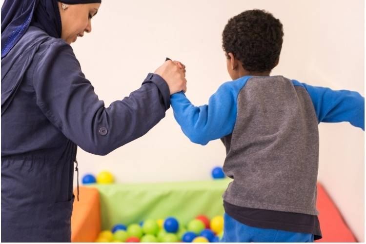 גננת ותלמיד משחקים בבריכת כדורים