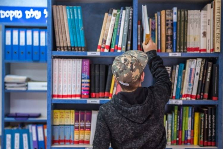 תלמיד בוחר ספר מהספרייה