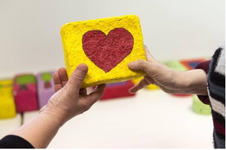 ידיים מחזיקות יצירת אומנות עם לב